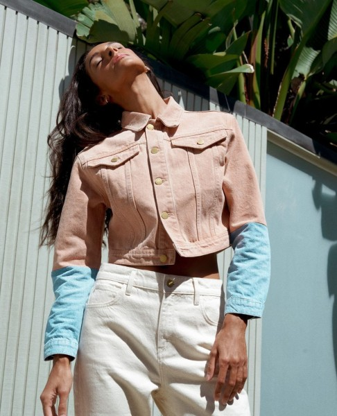 Woman wears a two-tone denim jacket and white jeans from Triarchy