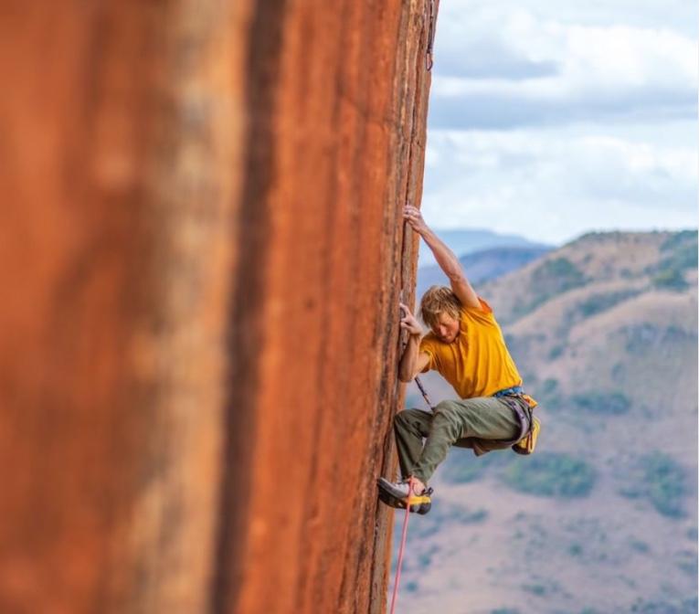 Man on mountain cliff with Patagonia fashion