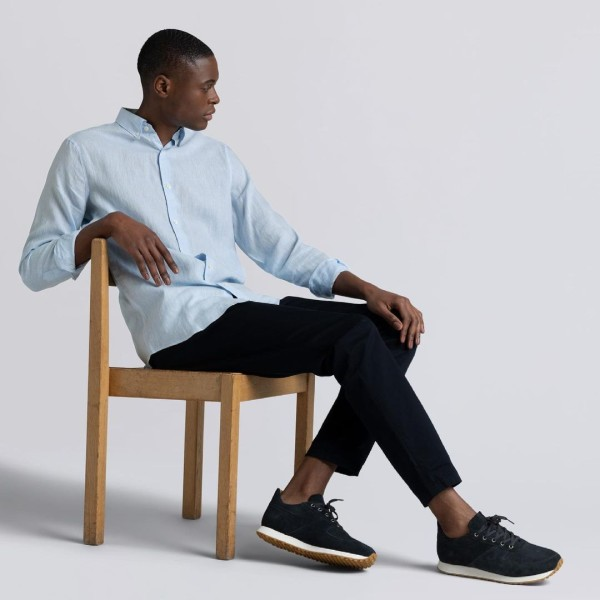 A man sits in a chair and wears sustainable fashion from ascetic
