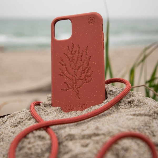Coral colored phone case in the sand