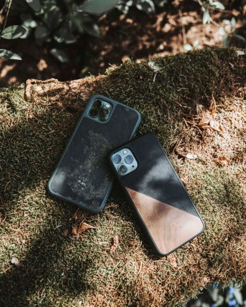 Two cell phone cases made of wood and stone in the forest