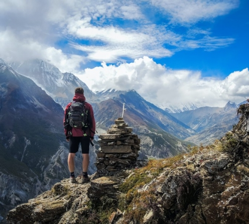 Man on a mountain with a sustainable backpack