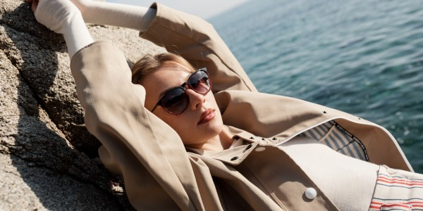 Woman lies by the sea and wears Sea2See sunglasses